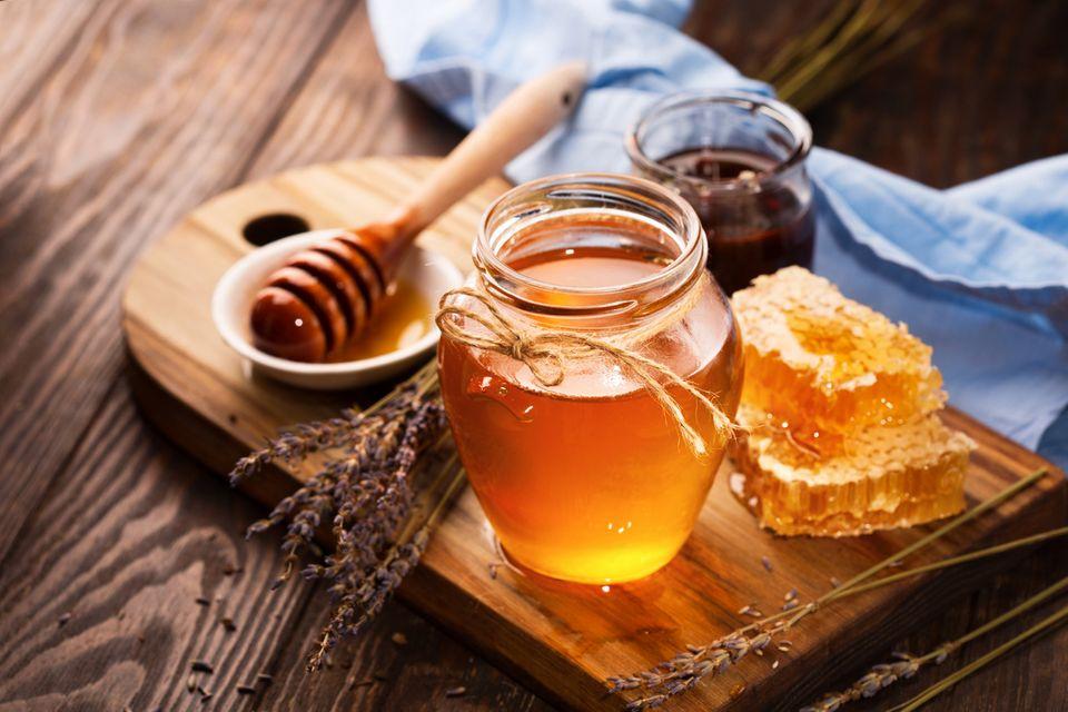 Honig im Glas mit einer Bienenwabe daneben