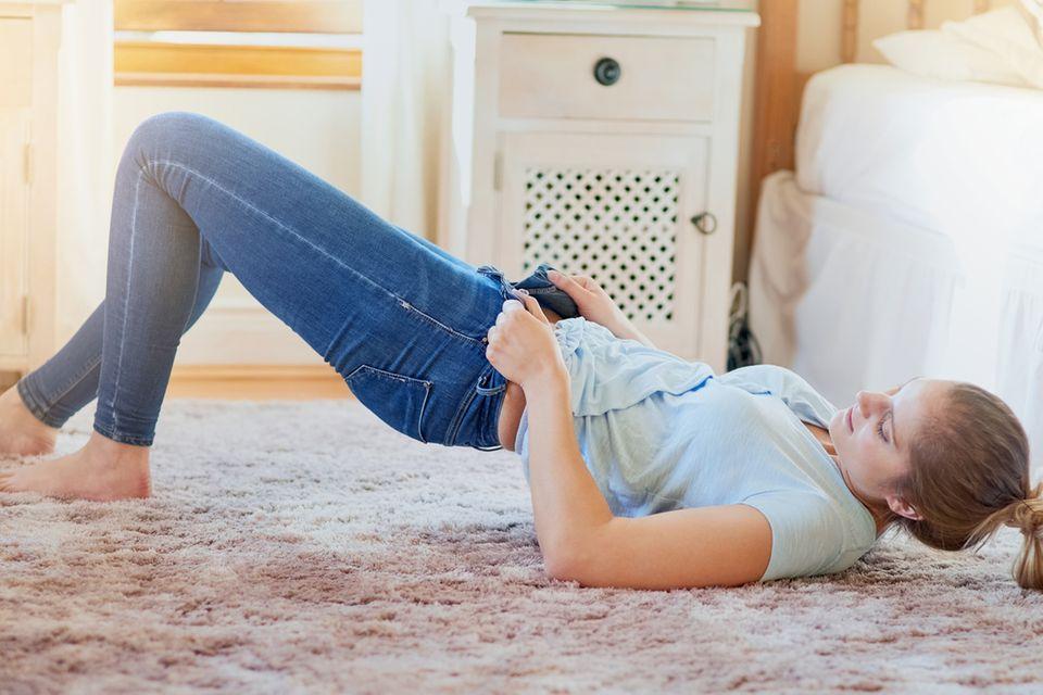 Frau liegt auf den Boden und zieht sich eine Jeans an
