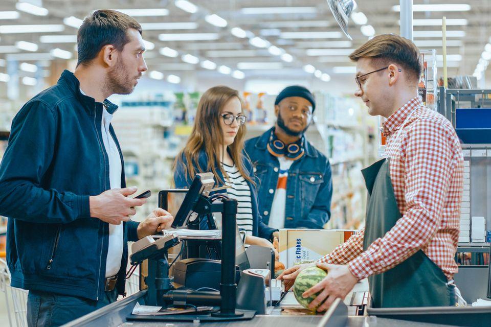 Kunden an der Supermarktkasse