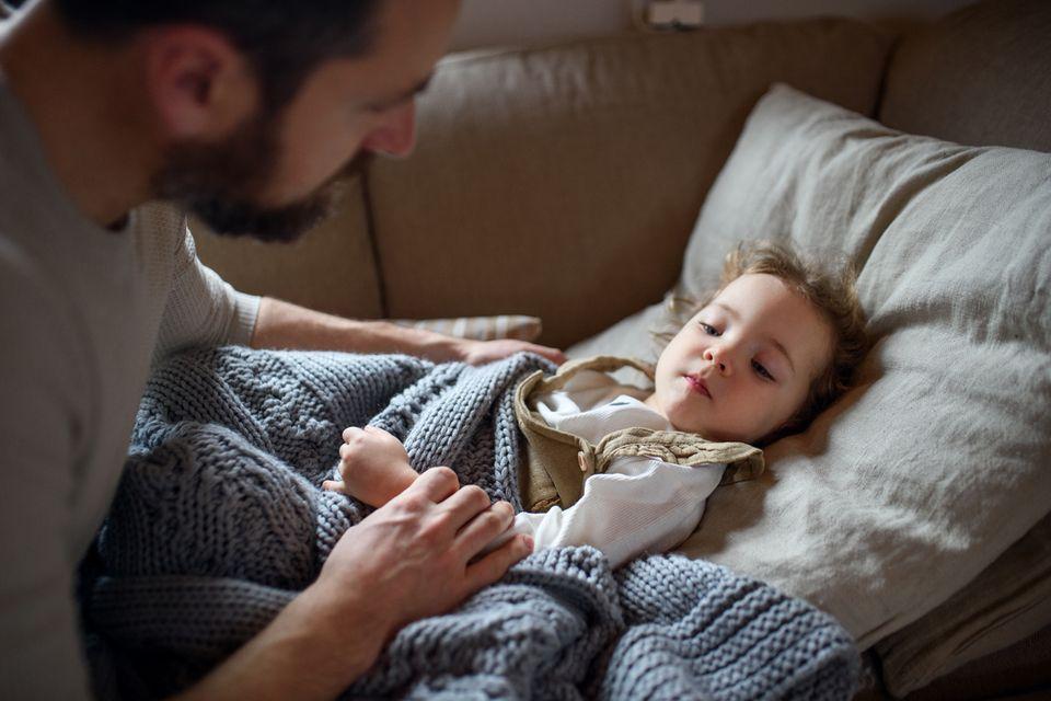 Vater kümmert sich um krankes kleines Mädchen auf dem Sofa, mit Vater