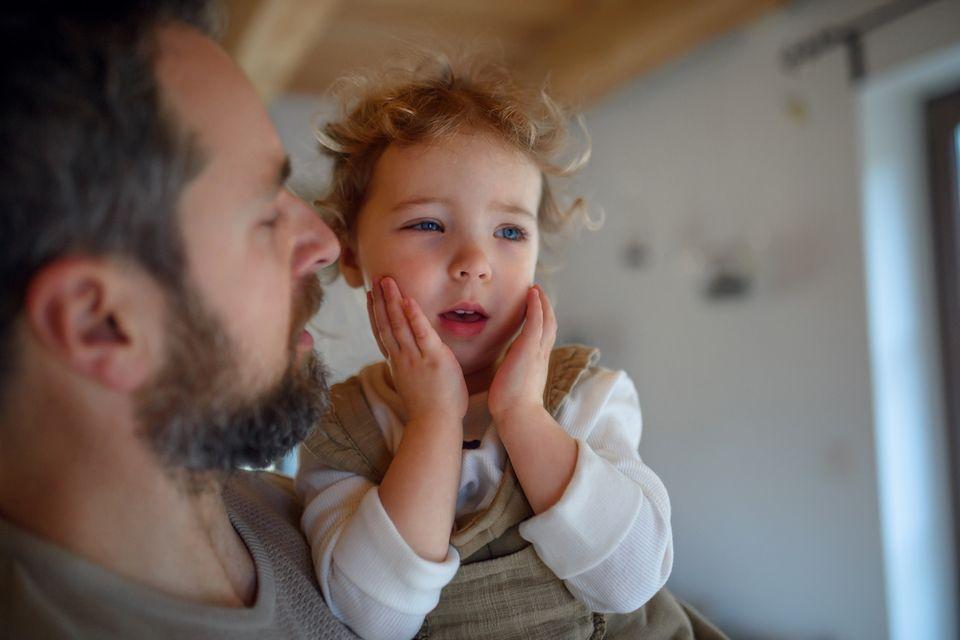 Vater hält kleines krankes Mädchen auf dem Arm