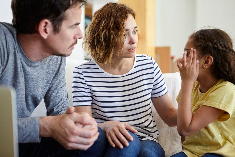 Eltern kümmern sich um Tochter mit Kopfschmerzen