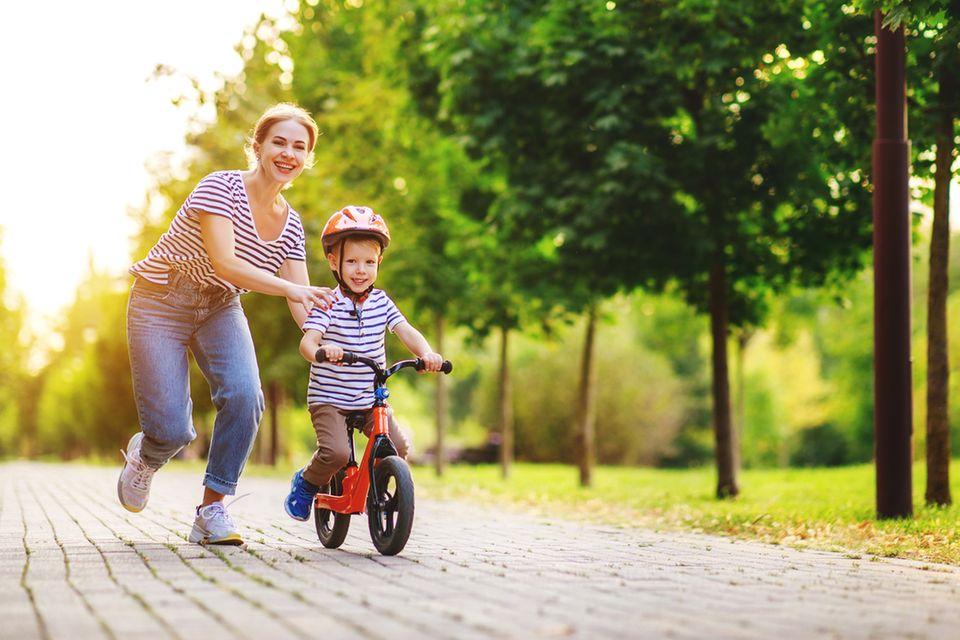 Mutter und Kind im Park beim Fahrradfahren