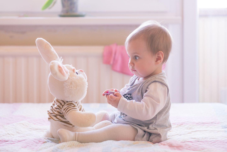 Baby staunt großen Stoffhasen an