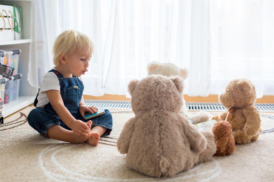 Kleinkind spielt mit seinen Kuscheltieren