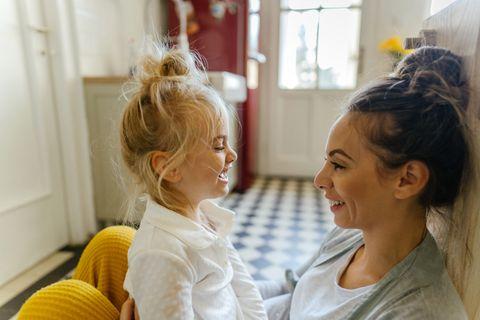 Mutter und Kind sitzen in der Küche auf dem Boden