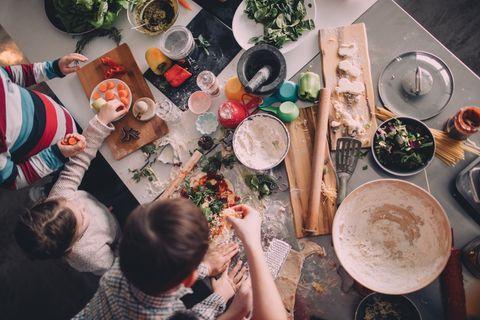 Familie belegt und backt zusammen Pizza