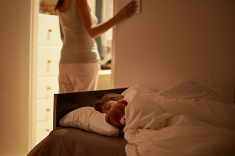 Mutter bringt ihren Sohn ins Bett
