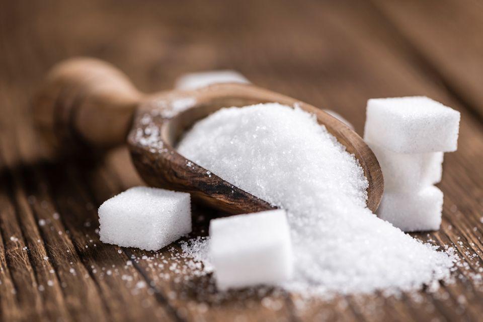Kelle Zucker und Zuckerwürfel auf einem Tisch
