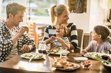 Eltern reden mit Kindern beim Essen über den Tag