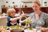 Sohn legt der Mutter frischen Salat auf den Teller