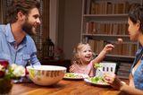 Tochter füttert Mutter am Esstisch