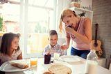 Mutter telefoniert am Esstisch
