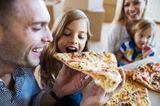 Familie isst Pizza und Tochter beißt beim Vater ab