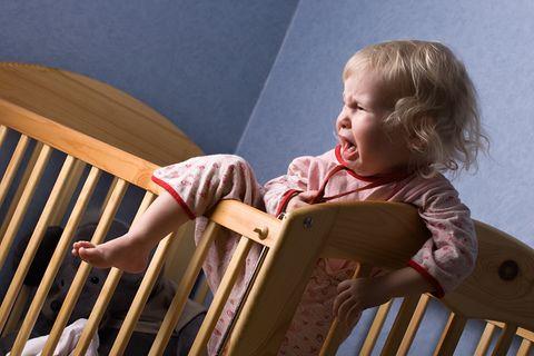 Kind klettert weinend aus dem Gitterbettchen