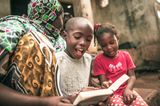 Junge in Afrika liest kleiner Schwester vor