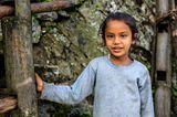 Mädchen im Himalaya steht in der Tür ihrer Wohnung