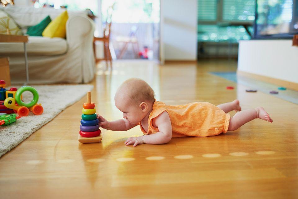 Baby liegt auf dem Bauch und spielt mit Ringen