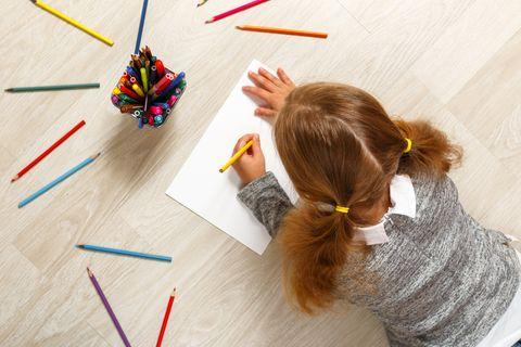 Mädchen liegt auf dem Boden und malt ein Bild