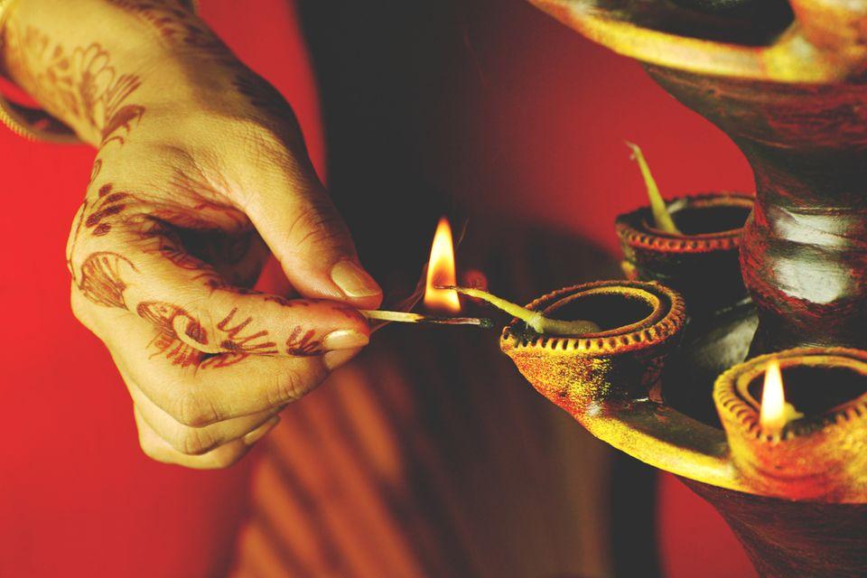 Frau mit Henna auf den Händen zündet eine Kerze an
