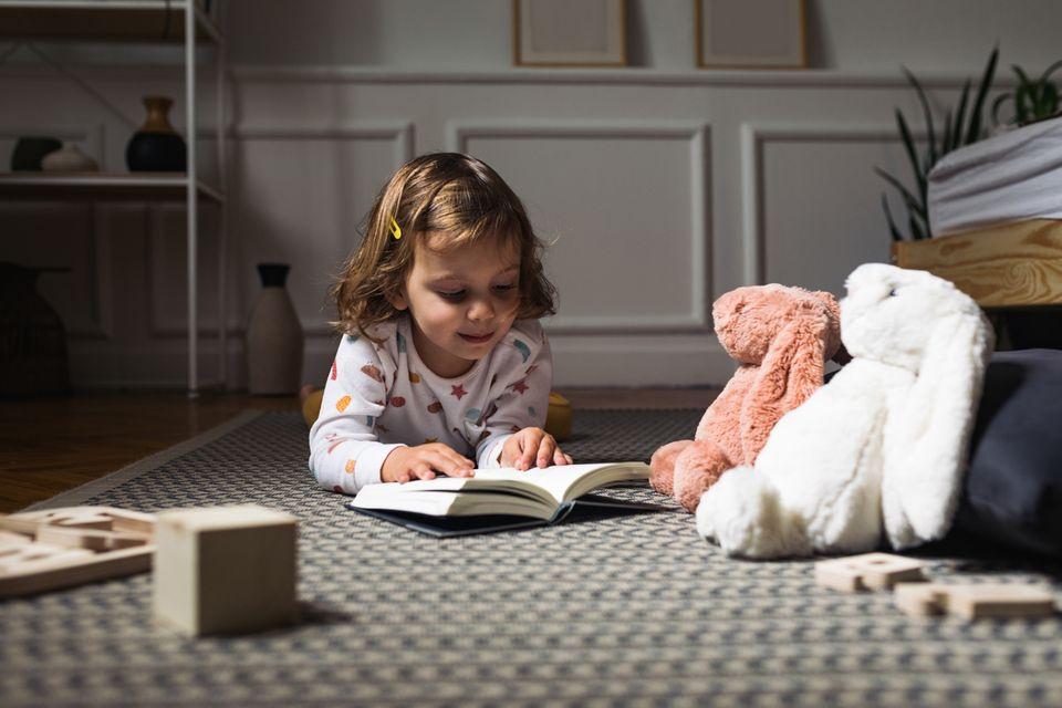 Kleines Mädchen liegt bäuchlings auf dem Boden und liest ein Buch