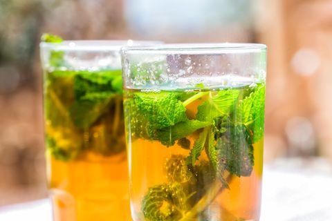 Zwei Gläser mit Pfefferminztee und Blättern
