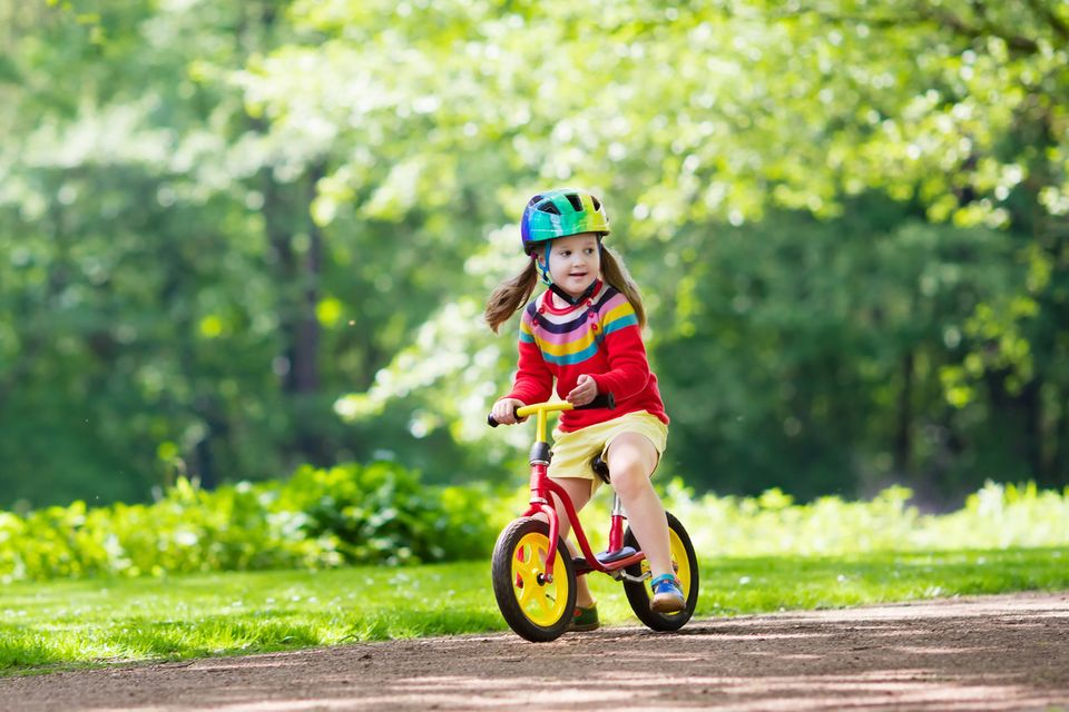 Mädchen ist lächelnd mit Laufrad auf Waldweg unterwegs