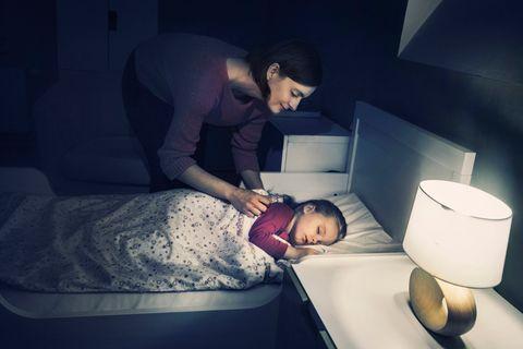 Mutter bringt ihre Tochter zu Bett