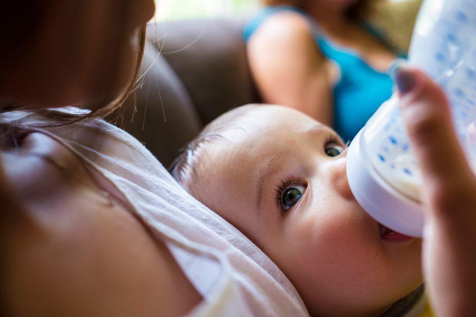 Baby trinkt aus Fläschchen und schaut seine Mutter dabei an