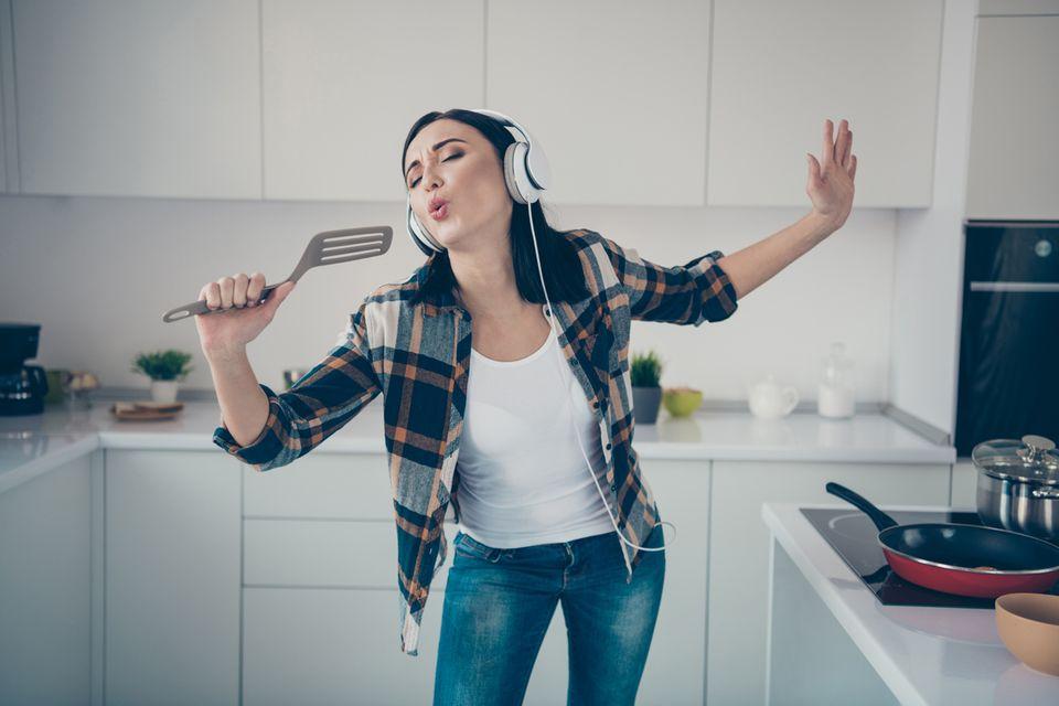 Frau in der Küche hört Musik und singt laut mit