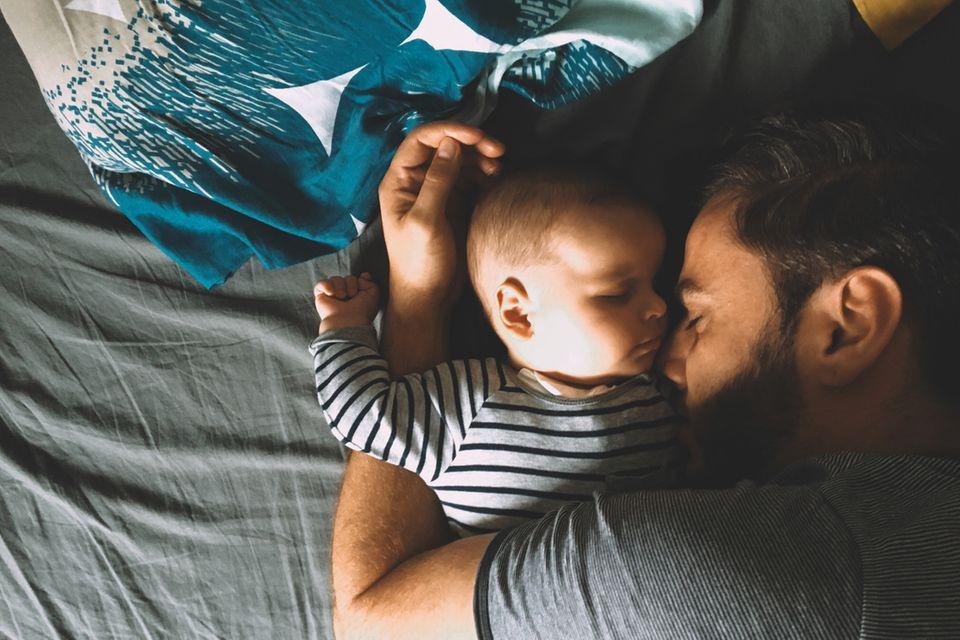 Baby und Vater schlafen im Bett