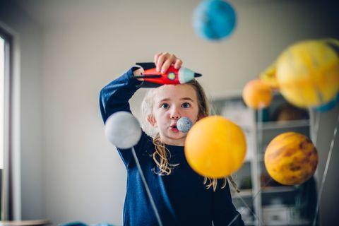 Mädchen spielt mit einer Rakete Astronautin