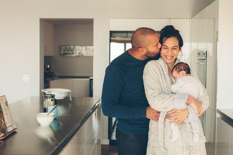 Junges, glückliches Paar mit Neugeborenem steht in der Küche