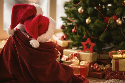 Kinder sitzen mit Weihnachtsmützen vor Weihnachtsbaum