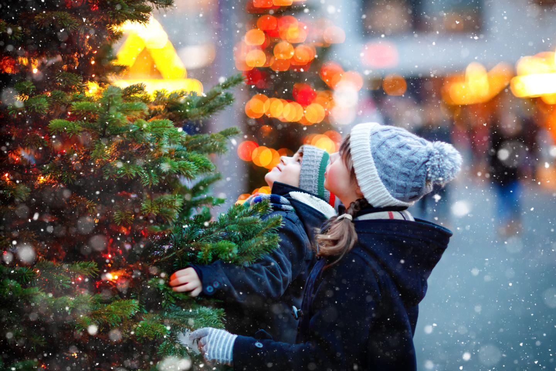 Zwei Kinder stehen vor Weihnachtsbaum