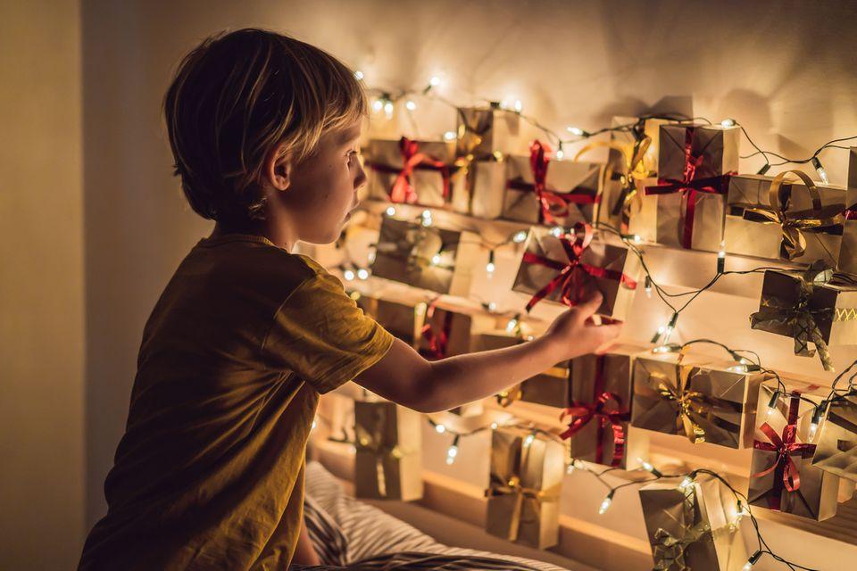 Junge öffnet Türchen am Adventskalender