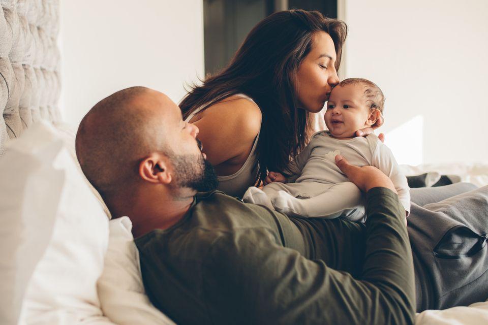 Junge Eltern schmusen mit ihrem Baby