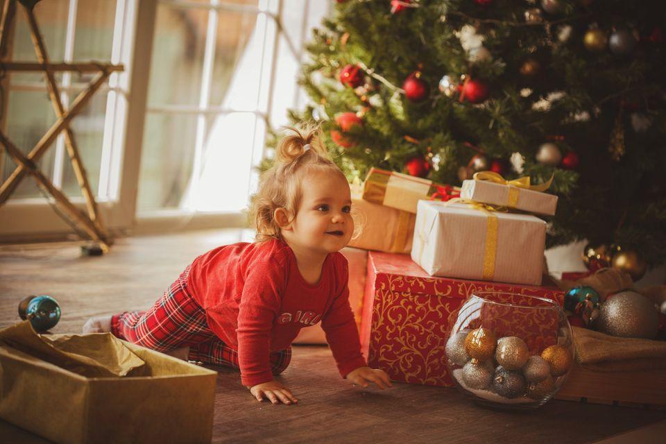 Baby krabbelt zwischen Weihnachtsbaum und Geschenken