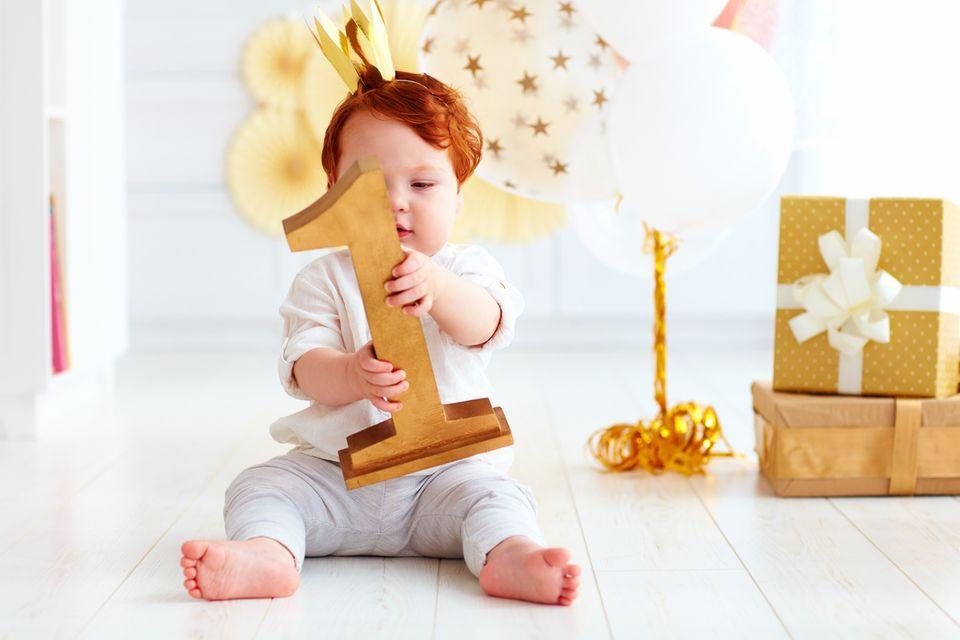 Kind feiert seinen ersten Geburtstag und hält eine große Eins in der Hand