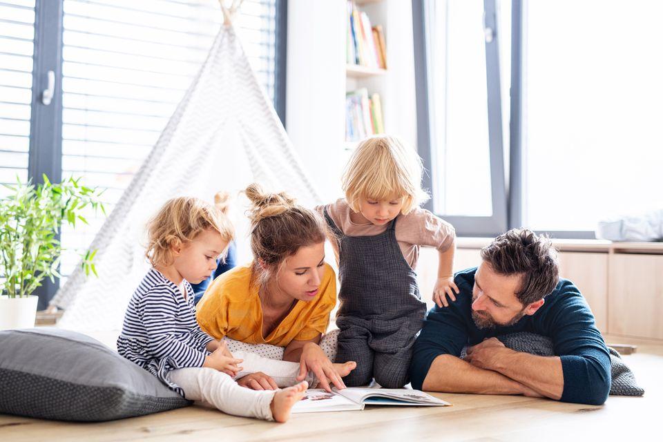 Junge Familie liest zusammen ein Buch