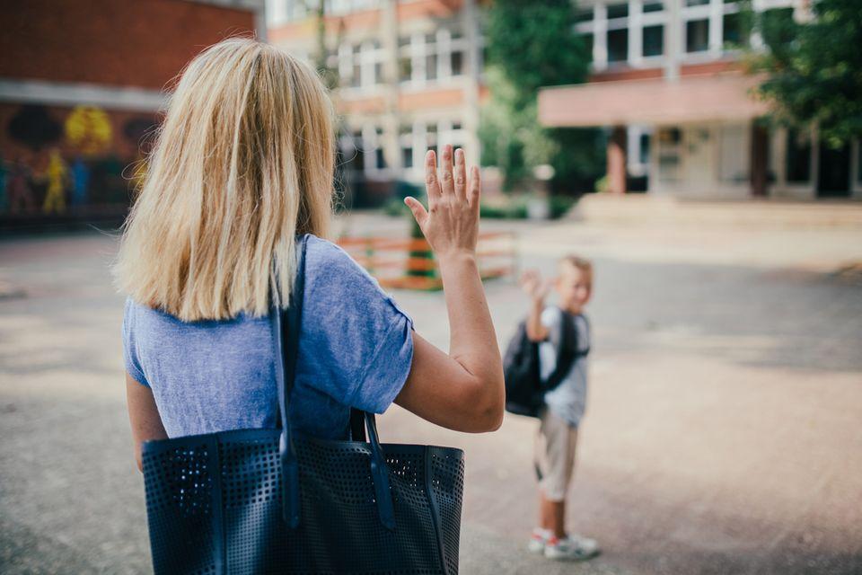 Mutter verabschiedet ihr Kind vor de Schule