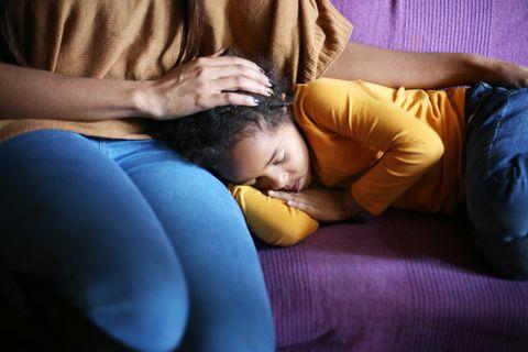 Kleines Mädchen schläft auf dem Sofa, seine Mutter streichelt es
