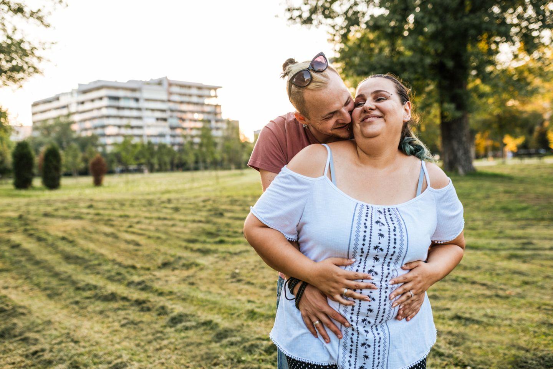 Plussize Schwangere wird von ihrem Freund umarmt