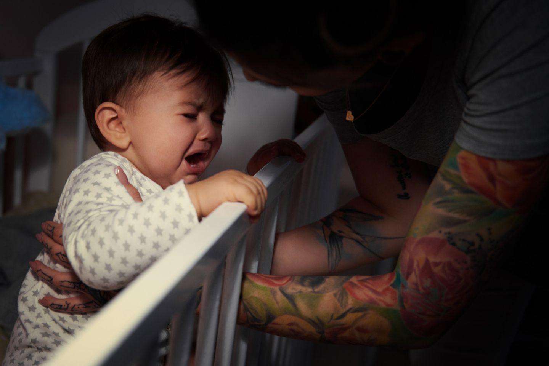 Mutter hebt schreiendes Baby aus dem Bett