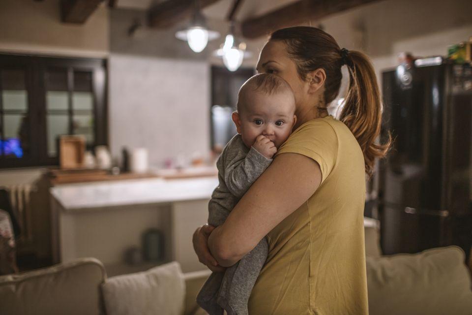 Mutter trägt nachts Baby durch die Wohnung