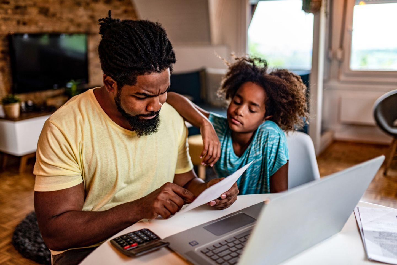Vater und Tochter sitzen am Computer und rechnen