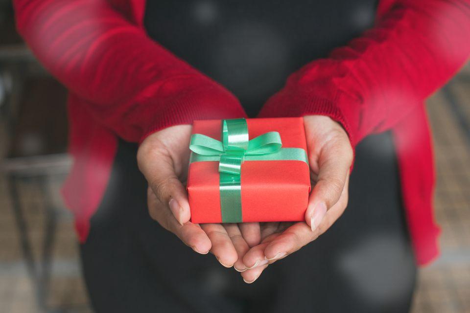 Eine Frau überreicht ein kleines Geschenk in die Kamera