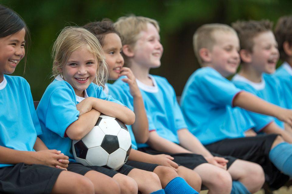 Mädchen und Jungen in Trikots sitzen beim Fußball auf der Ersatzbank