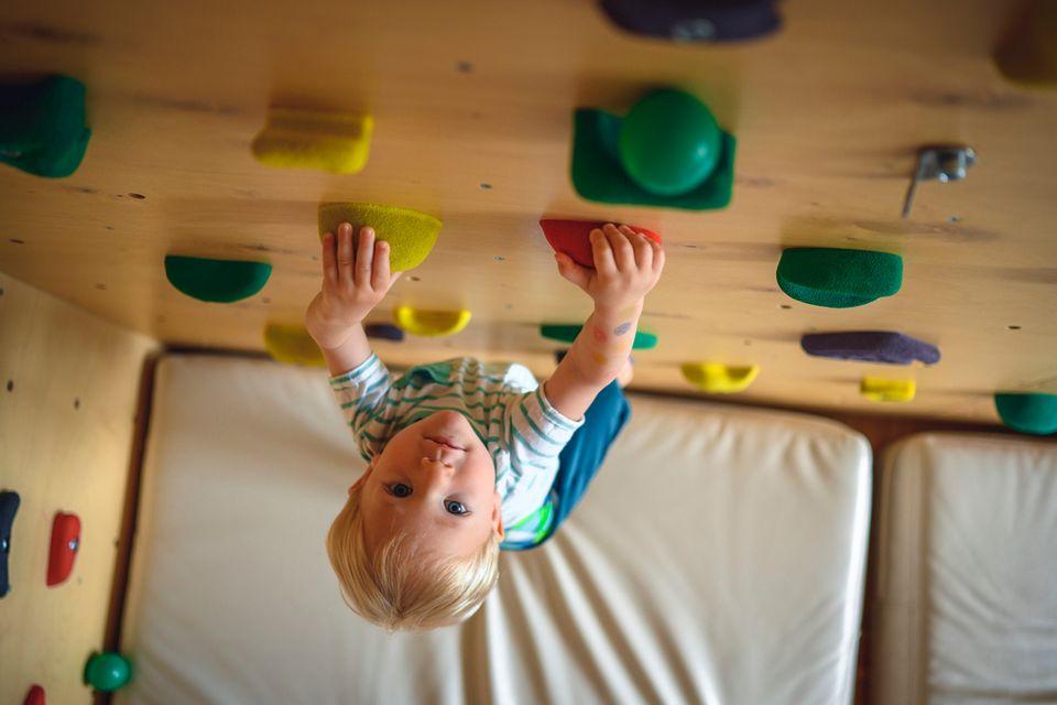 Kleiner Junge klettert an der Kletterwand