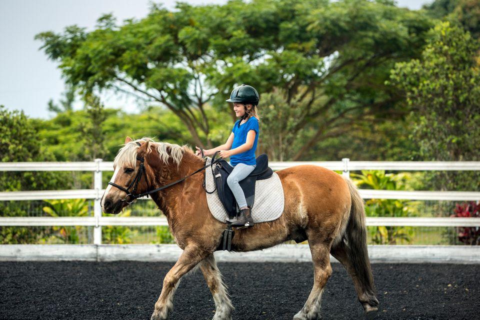 Maedchen reitet auf einem Pony